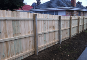 A timber fence with a house behind it
